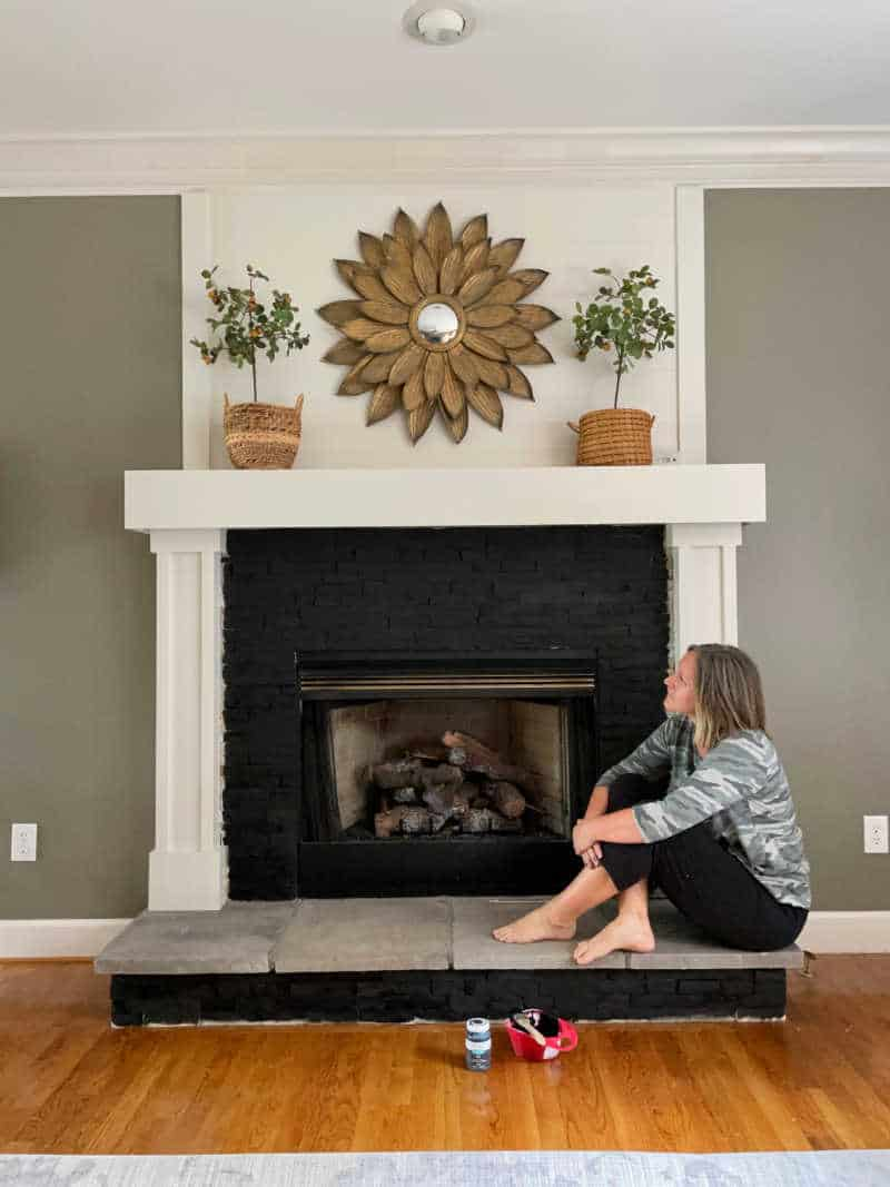 Sonya looking at the painted fireplace during the process